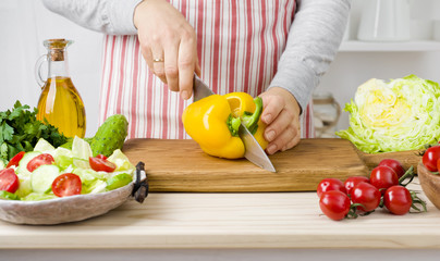 Woman hands cutting vegetables on board in kitchen cooking salad