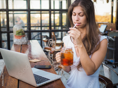 digital nomad girl enjoying drink while working on a laptop in a coffee shop