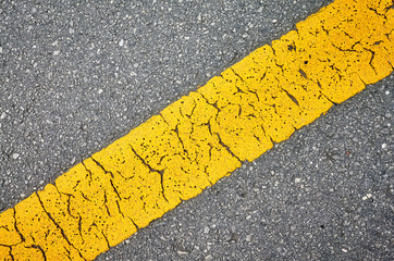 Close up picture of an asphalt road with yellow lane.