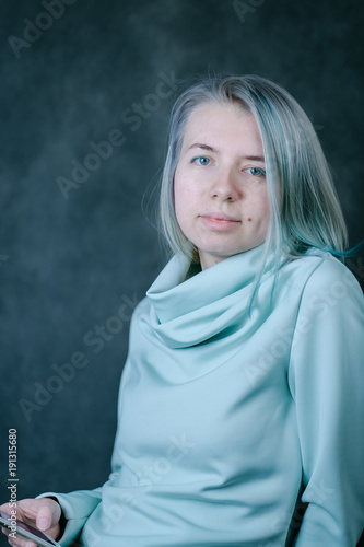 Beautiful woman with colouring blue and green blonde hair in photo studio in salon of hairstyle with phone in hand