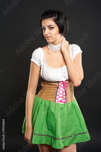 Beautiful woman in german beer girl costume over black background