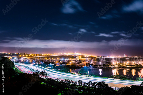 Fotobehang Nacht snelweg cars in motion on a lighted bridge and highway over the sea with anchored sailing boats in a marina of Auckland in New Zealand with a cloudy sky
