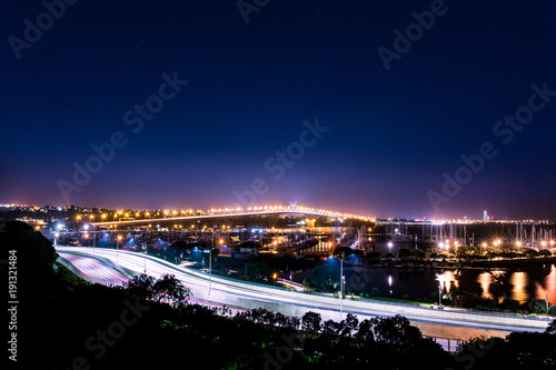 In de dag Nacht snelweg cars in motion on a lighted bridge and highway over the sea with anchored sailing boats in a marina of Auckland in New Zealand with a Starry sky