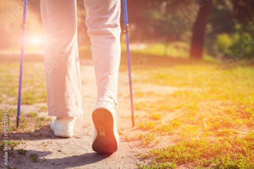 Foto op Canvas Oranje Time for resting. Close up of elderly woman holding crutches in hands while having adorable walk outdoors