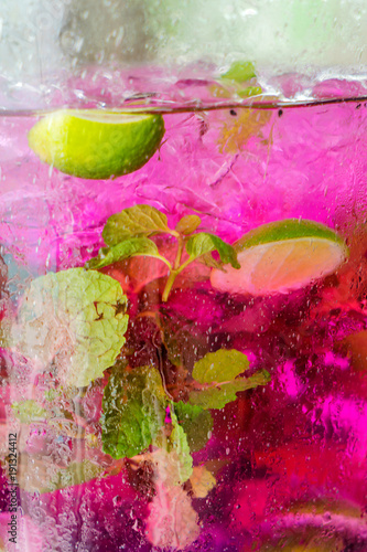 Pink tea karkade with mint and lime. Macro in the street in the decanter.