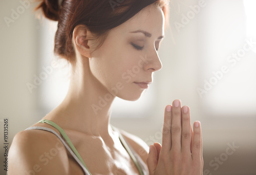 Fototapeta Relaxed young sportswoman doing yoga and meditating in studio