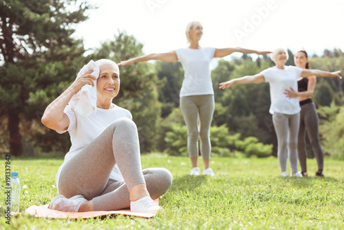 Sport exercises. Happy delighted positive woman smiling and holding a towel while having a break from the workout