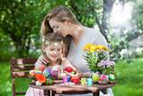 Kind bemalt Ostereier und Mutter küsst sie lieb - 191354893