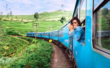 Happy smiling woman looks out from window traveling by train on most picturesque train road in Sri Lanka - 191358661