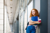 Young redhead student girl on the way to classes with cup of coffee - 191361412