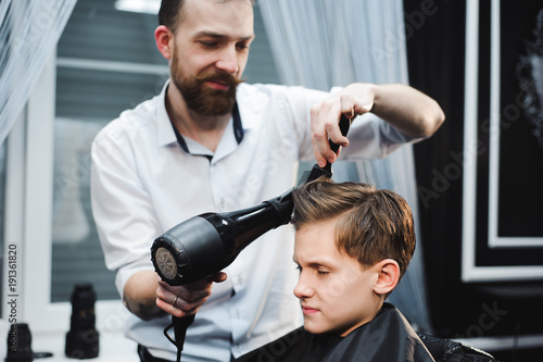 Master cuts hair of a boy in the barbershop, hairdresser makes hairstyle for a boy