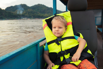 Tourist boy enjoy boat trip. Laos.