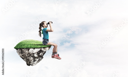 Concept of careless happy childhood with girl looking in binoculars