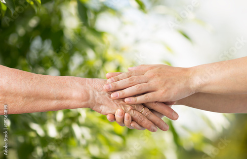 Fotobehang Hoogte schaal close up of senior and young woman holding hands