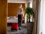 Young businesswoman arrives in a hotel room with red suitcase - 191365854