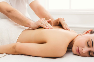 Closeup of hands massaging female shoulders and back © Prostock-studio
