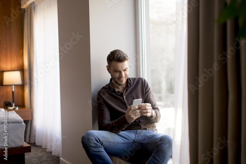 Young businessman with mobile phone by window