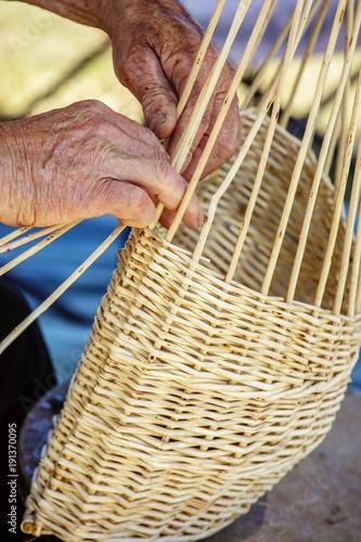 Man's hands making a wicker basket under sunny day