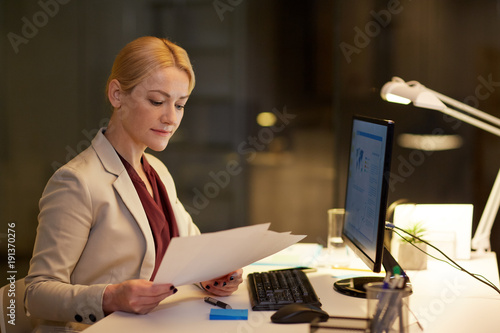Wall mural businesswoman with papers working at night office