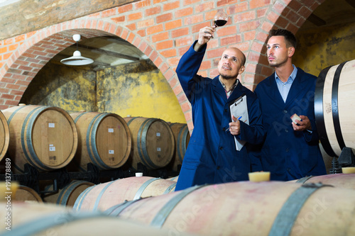 Winery employees checking up wine sample