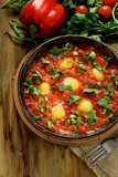 Fried eggs with tomato sauce and parsley in a cast iron pan. Shakshuka a traditional meal of the Jewish cuisine - 191379656