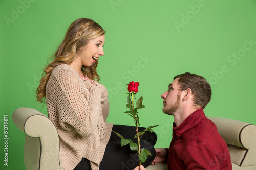Young couple talking about marriage. Studio shot with mint green background.