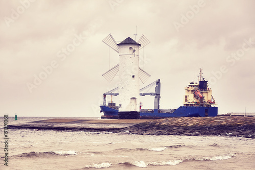 Cargo ship leaves the port of Swinoujscie in Poland, color toned picture.