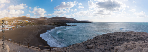 In de dag Canarische Eilanden panorama high angle view of town of Ajuy on island of Fuerteventura, Spain under blue sky with cliffs on coast and mountains in background