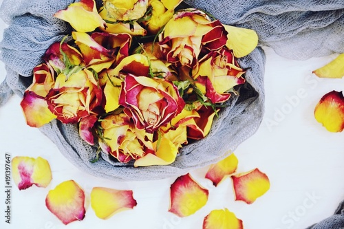 Foto Murales Dry Yellow and Pink Roses on the white background. Flat lay, top view