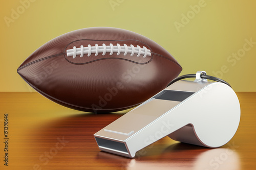 american-football-ball-with-whistle-on-the-wooden-table-3d-rendering