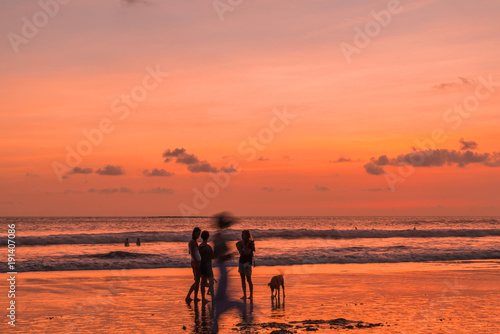 Foto op Plexiglas Oranje eclat Beach with people in sunset