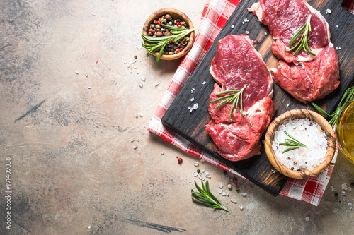 Aluminium Steakhouse Raw beef steak with herbs on stone table. Top view.