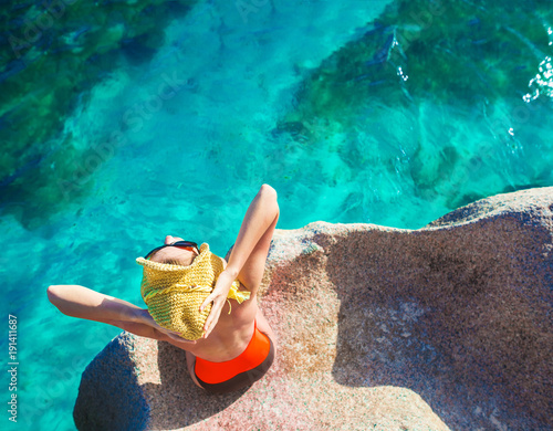 beautiful long haired woman in onepiece swimsuit relaxing on the rocks over the sea. Mahe Island, Seychelles