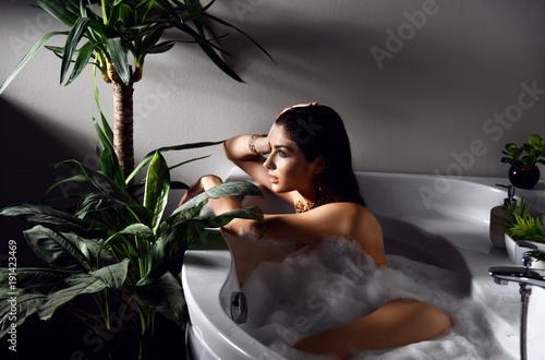 Young beautiful woman lying in bathtub and taking bath