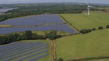 Rising aerial footage flying over solar panel and windmill energy farm - 191429829