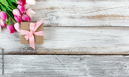 Pink springtime tulips and gift box on white rustic wooden boards