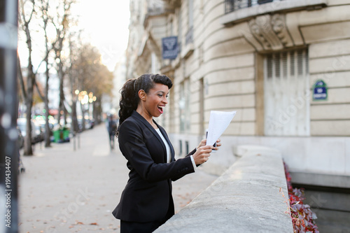 African American talking on silver gadget and walking on street near office building with papers in hands during lunch break. Daughter knew about mother s arrival. Young black-haired woman with bang