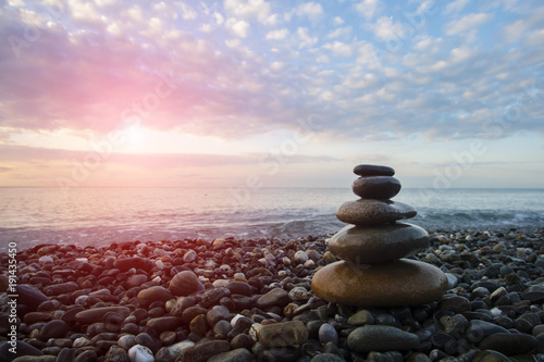 Staande foto Zen Pyramid of pebbles on the beach against the sea.