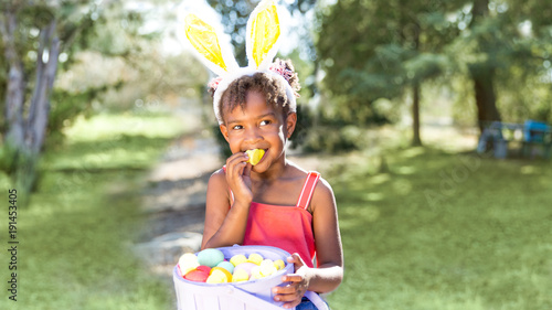 Cute African American girl eating and enjoying Easter candy wearing bunny ears
