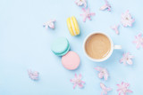 Cake macaron or macaroon, pink flowers and coffee on blue pastel background top view. Creative and fashion composition. Flat lay style. - 191459239