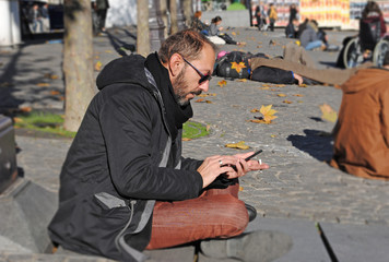 Man portrait; man is sitting on the street and is typing on his smartphone; people, technology and lifestyle concept.
