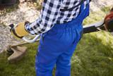 Unrecognizable gardener with weedwacker cutting the grass in the garden - 191478644