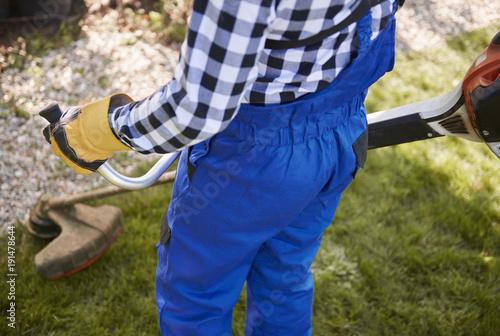 Sticker Unrecognizable gardener with weedwacker cutting the grass in the garden