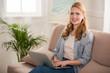 beautiful young woman using laptop and smiling at camera