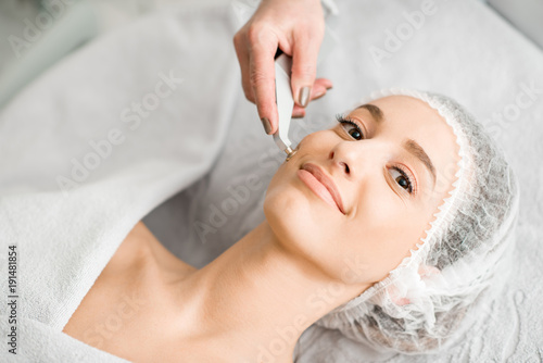 Fotobehang Spa Young woman during the facial treatment procedure in the cosmetology office