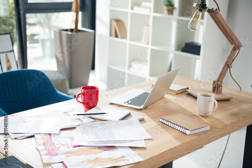 messy fashion designer workplace with laptop and sketches