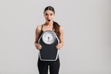 Photo of brunette athletic woman holding scale and expressing surprise on face, isolated over gray background - 191483807