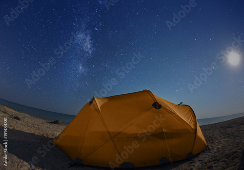 orange tent on the beach at night under the starry sky. Travel photography concept