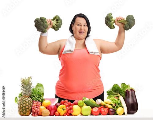 Overweight woman exercising with broccoli dumbbells behind a table with fruit and vegetables - 191486469