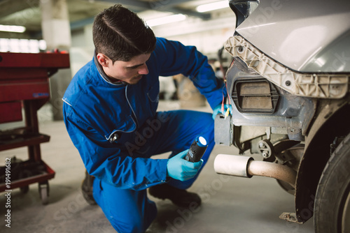 Mechanic man inspecting a vehicle in a mechanical workshop